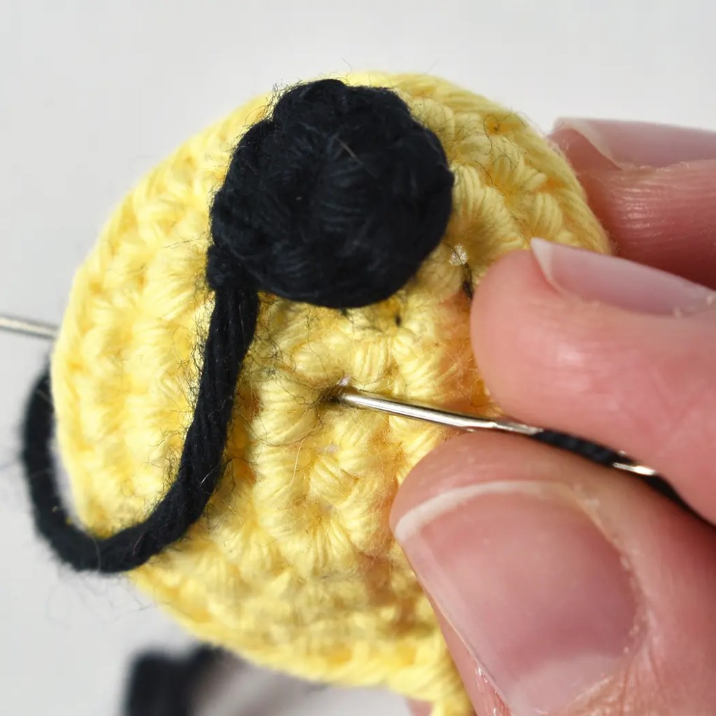 Close up of Monsieur Bear amigurumi dolls muzzle assembly. The crochet nose and muzzle are being attached.