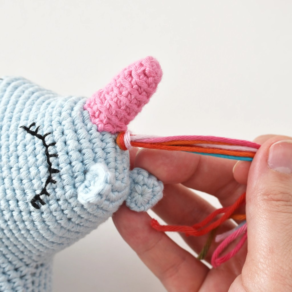 Attaching the rainbow hair for the free amigurumi unicorn pattern