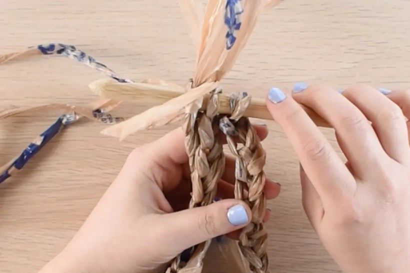 A wooden crochet hook is inserted through the top of 3 chain ropes. The chain ropes are made with 3 strands of brown plastic bag yarn.