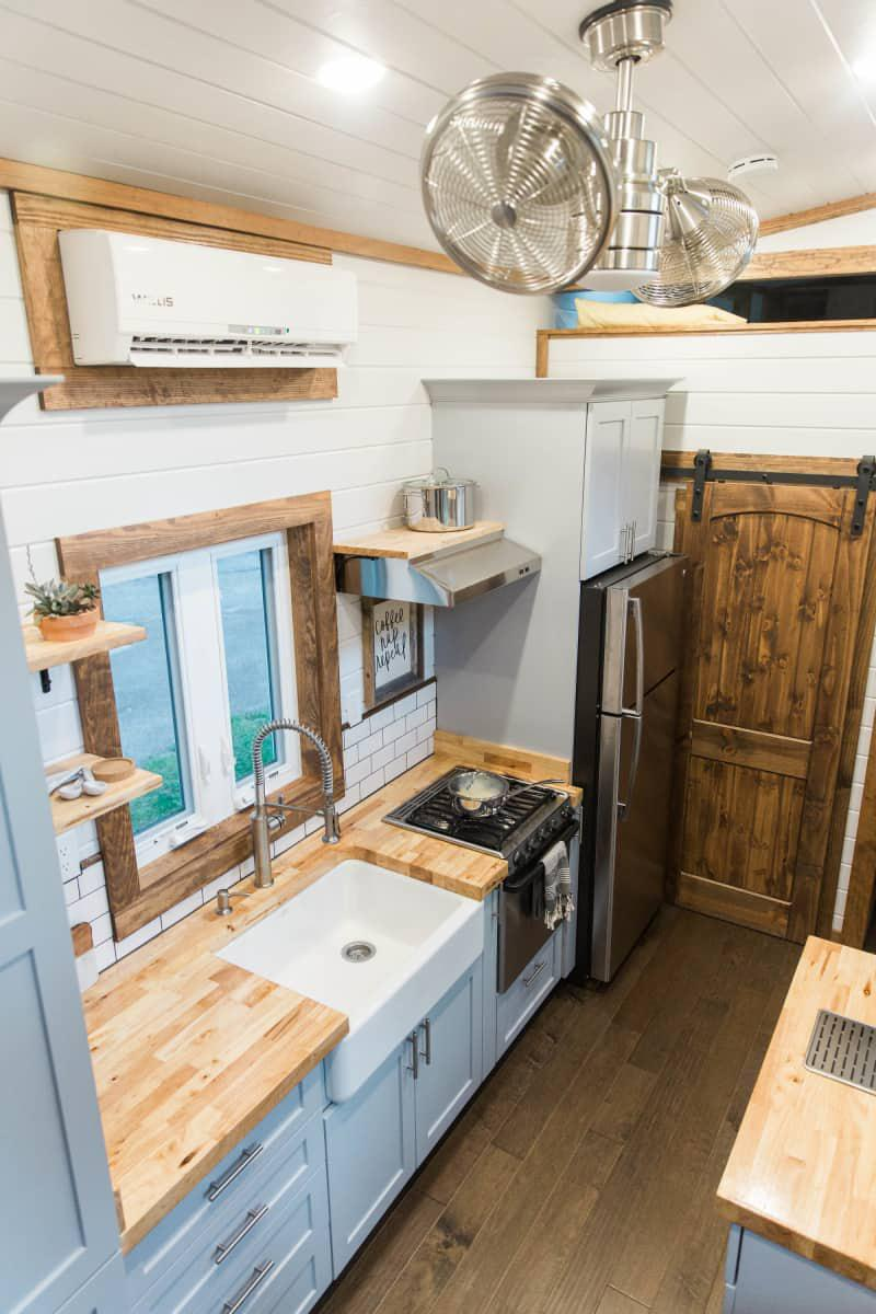 medium resolution of and speaking of a cup of tea the kitchen area is big for a tiny house and boasts standard sized appliances we love the farmhouse sink and wood counter