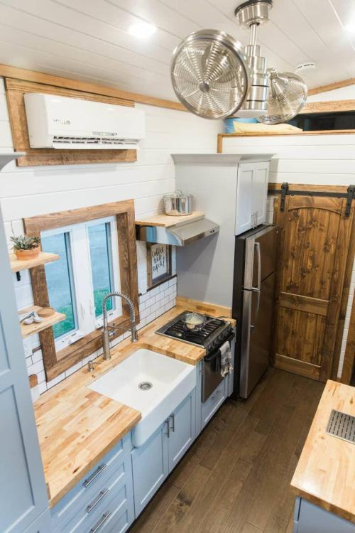 small resolution of and speaking of a cup of tea the kitchen area is big for a tiny house and boasts standard sized appliances we love the farmhouse sink and wood counter