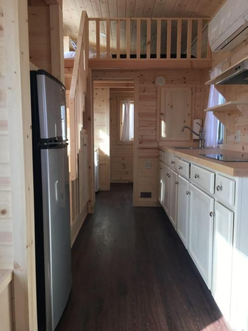 small resolution of the kitchen in this tiny house has plenty of counter tops for food prep and cooking it also shares space with the living room making it perfect for