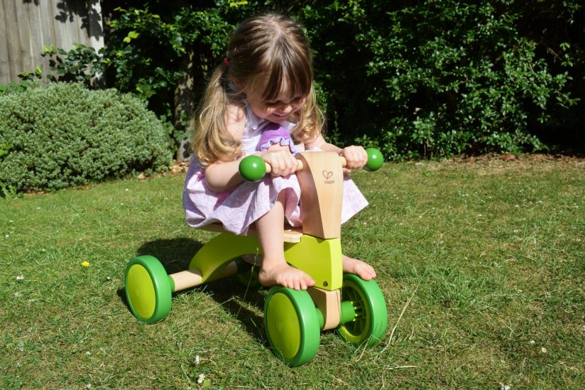 Hape Scoot Around - wooden rider - in use by her