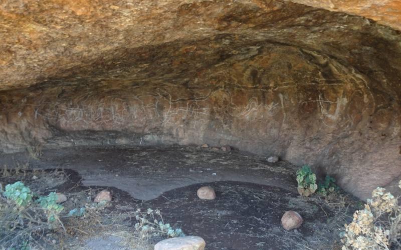 """Caverna con all'interno arte rupestre aborigena al punto panoramico """"The White Cross"""" lungo la Great Central Road nel deserto australiano"""