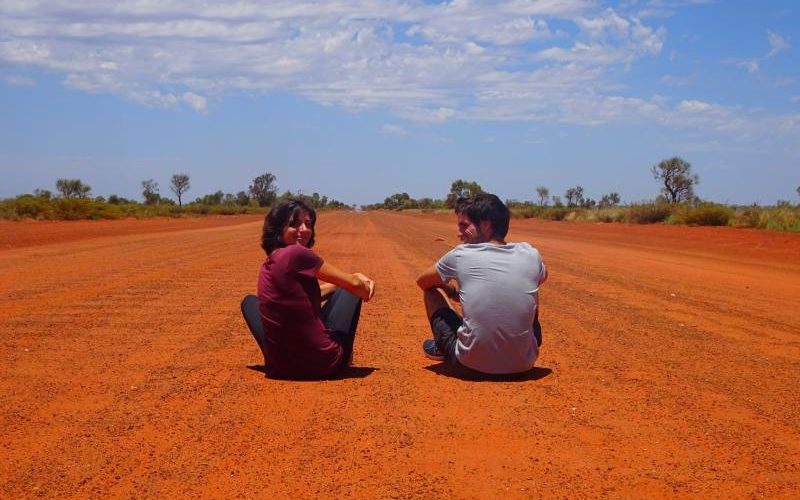 Noi due seduti sulla terra rossa del deserto australiano durante l'On the Road della Great Central Road