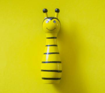Abeja de juguete de color amarilla sobre un fondo amarillo