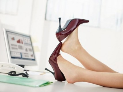 En la foto una mesa de trabajo con un PC encendido y dos pies de mujer sobre la mesa