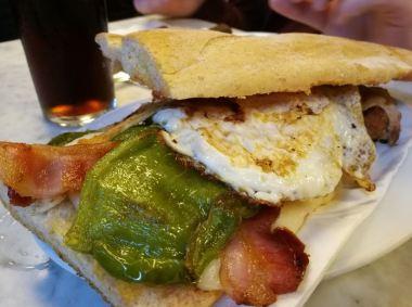 En la foto un bocadillo en pan de chapeta donde vemos huevo frito, pimiento verde, bacon y queso