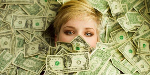 En la foto se ven los ojos y parte del pelo de chica rubia inundada de billetes