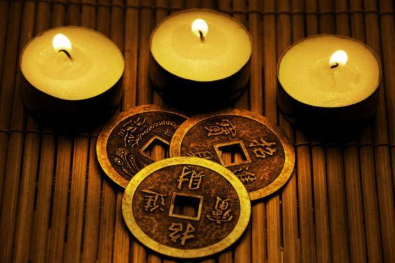 Imagen con las tres monedas del I Ching y tres velitas encendidas sobre una base de madera
