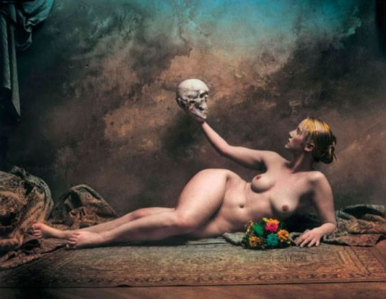 Foto artística de una mujer desnuda recostada en el suelo mientras con su mano derecha sujeta una calavera humana