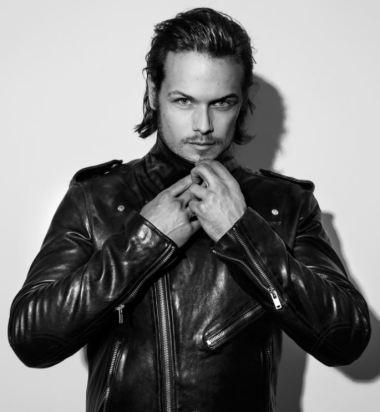 Foto medio plano de Sam Heughan. Foto en blanco y negro. LLeva puesto una chaqueta de piel.