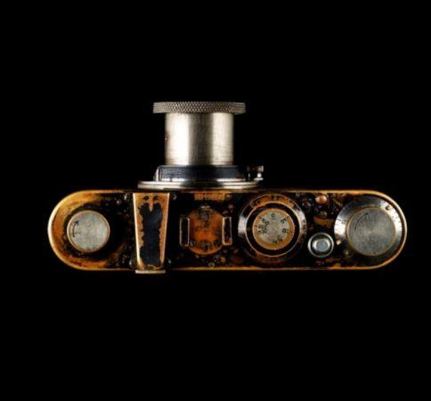 Foto desde una perspectiva en picado de una cámara reflex antigua de 135 mm, sobre un fondo negro.