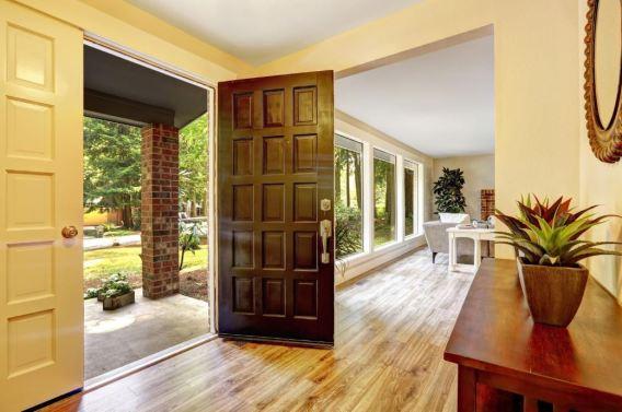 Imagen del interior de una casa con mucha luz, ventanales grandes con un trozo de jardín en el exterior ante la puerta de entrada.