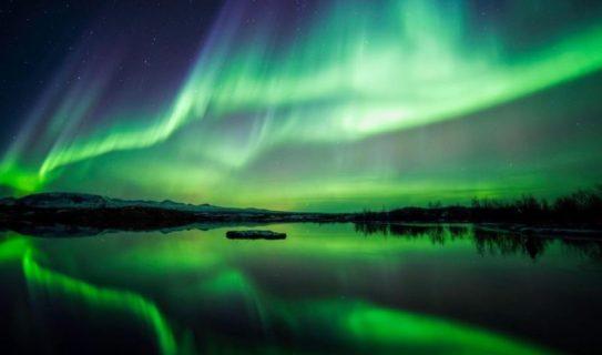 Aurora boreal reflejada en un lago. Foto espectacular con fondos azules y verdes.