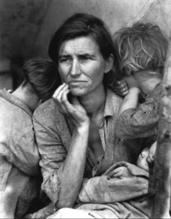 Foto en blanco y negro de una madre con pose preocupada rodeada de tres de sus hijos.