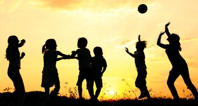 Foto a contraluz donde se ve la silueta de varios niños jugando con una pelota