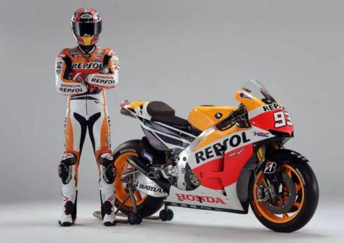 En la foto el piloto Marc Márquez con el mono y el casco puesto al lado de su moto de Moto GP