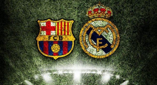 En la imagen sobre el césped de un campo de fútbol los escudo del Barça y del Real Madrid