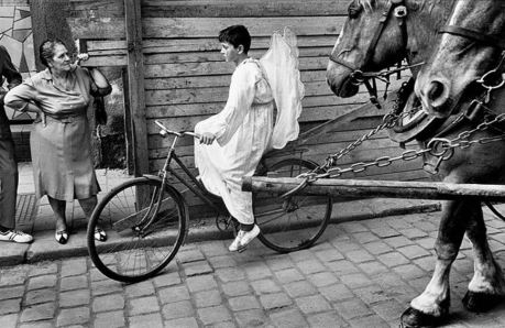 Foto en blanco y negro de un niño disfrazado de ángel con alas paseando en una bicicleta mientras una mujer le mira