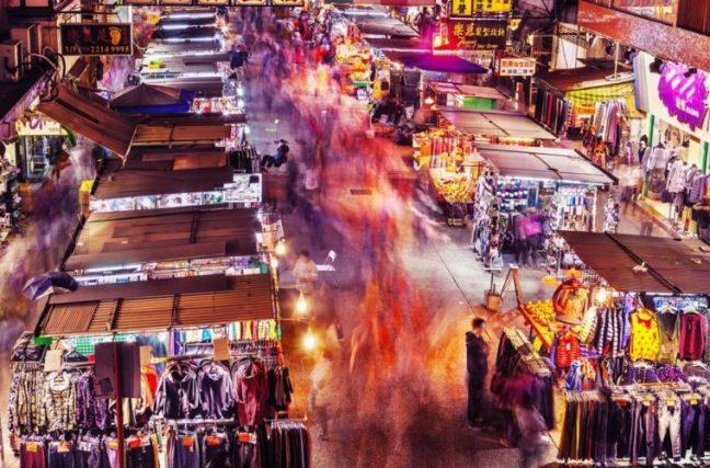 Tiendas de ropa puestas en la calle y gente comprando y paseando por ellas