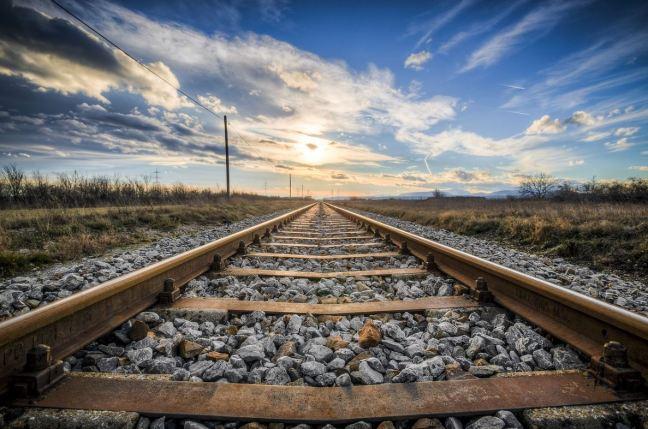Aparece una vía de tren que se extiende hasta el horizonte con un cielo azul y nubes blancas en la lejanía