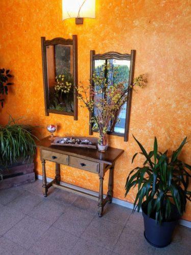 La entrada del restaurante Coll de Condreu es acogedora, con una bonita pared naranja y muebles rústicos