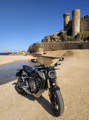 En la foto, la moto Honda CB650R con el castillo de Tossa de Mar al fondo