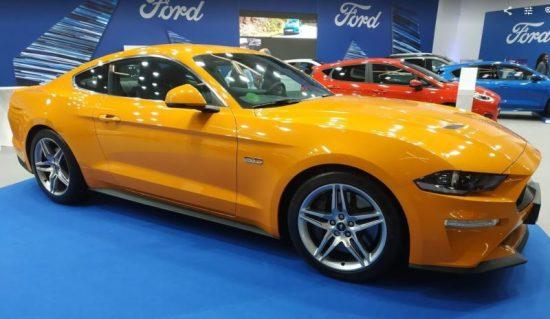 En la foto un Ford Mustang en color naranja visto desde el lateral