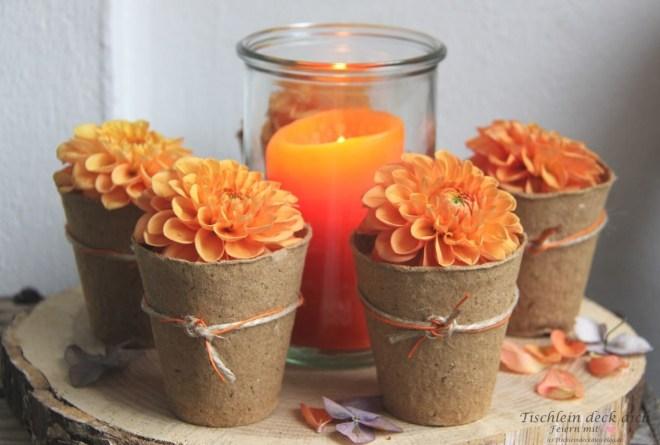 herbstliche Blumendekoration mit orangen Dahlien