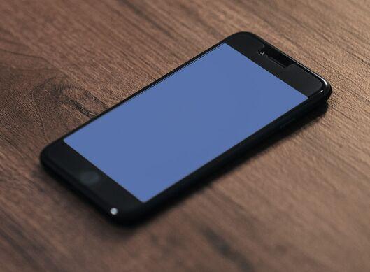 Jet Black iPhone 7 On The Desk Mockup PSD