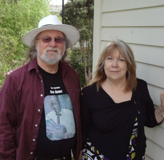 Beverley and Alan Young standing next to a weatherboard wall.