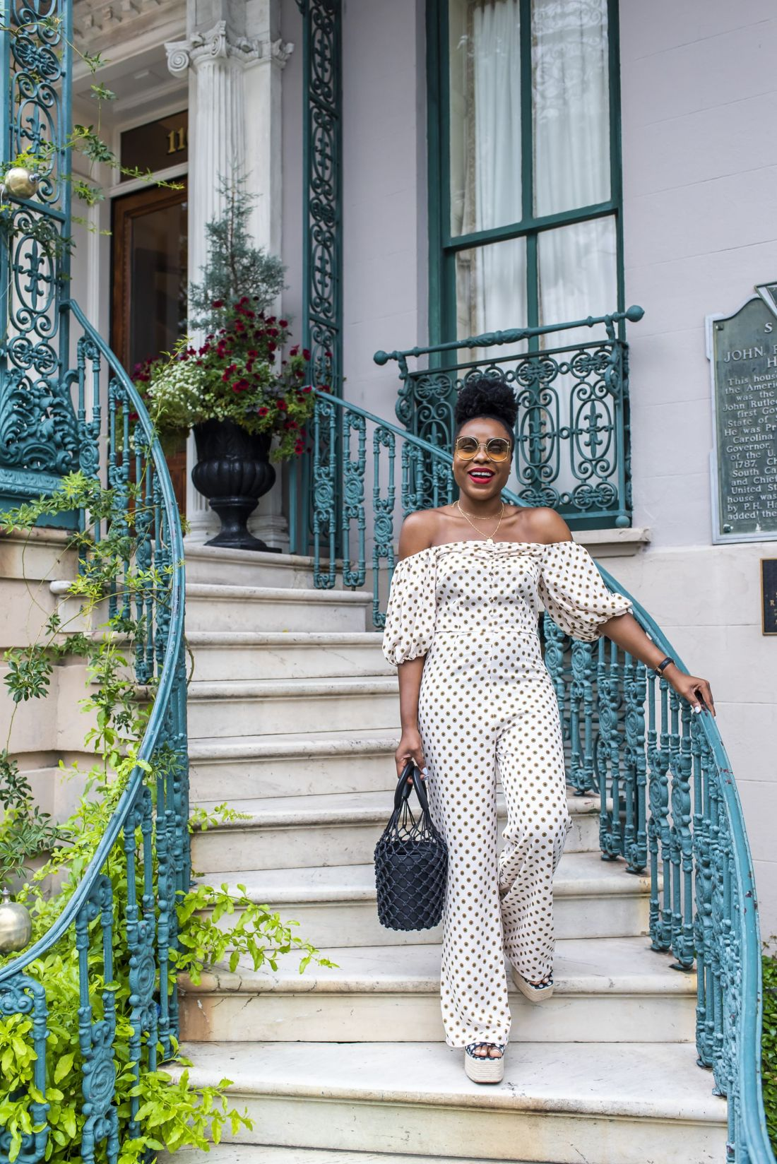 woman in polka dot jumpsuit on stairs