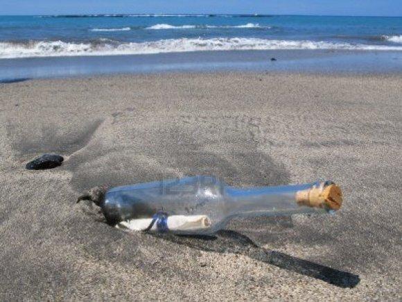 8313249-bouteille-avec-un-message-sur-le-sable-noir-de-le-ile-de-tenerife-iles-canaries
