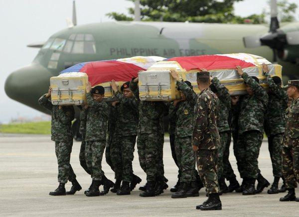 Les troupes des forces spéciales portent les cercueils recouverts du drapeau des militaires compatriotes tués dans des affrontements avec les rebelles musulmans.