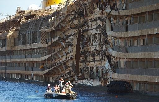 Les travailleurs de la société américaine Titan récupération et la firme italienne Micoperi inspecter l'épave du Concordia navire de croisière Costa après avoir été transporté hors de l'eau, dans le port de Giglio le 18 Septembre 2013