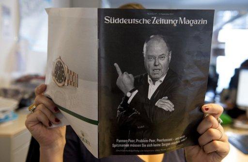 Une femme tient un supplément du magazine de Süddeutsche Zeitung représentant Peer Steinbrück donnant le majeur le 13 Septembre 2013.