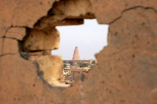 Une vue du minaret en spirale de la Grande Mosquée de Samarra vu en 2008 à travers un mur touché par des tirs d'obus.