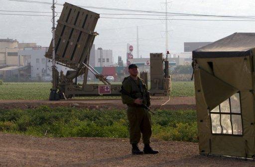 """Un soldat israélien se trouve en face d'un système de défense antimissile  """"Iron Dome"""" courte portée à proximité de Haïfa, le 6 mai 2013."""