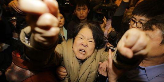 « Meurtriers ! Meurtriers ! », a hurlé une femme, retenue à grand-peine par les personnes l'accompagnant. | REUTERS/JASON LEE