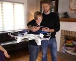 dad and son flying drone indoors