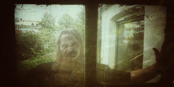 Asgeir poserer i gjennom et vindu i Baglerstredet.