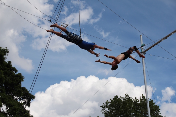 Two people linking hands on trapeze