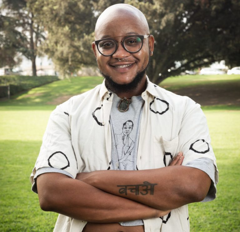Jaden smiles genuinely, posing with his arms crossed in brown circular glasses and a white button up shirt with black circles that he wears over a gray graphic t-shirt. Behind Jaden is a field of green grass and tall trees.