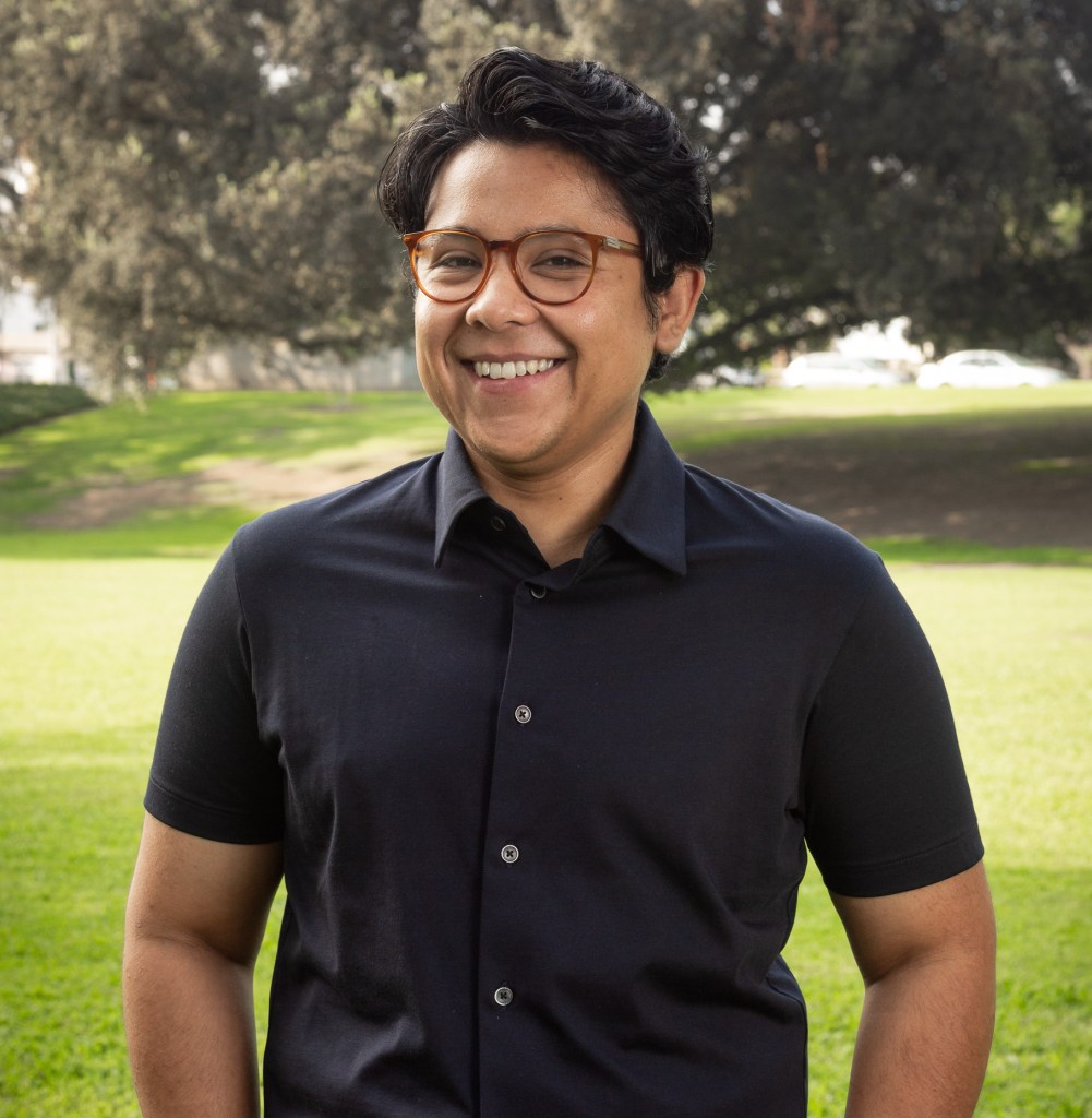 With a huge smile on their face, Lylliam stands in a black button up shirt and brown glasses in front of a field of green grass and tall trees.