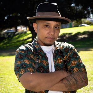 Jovan poses with his arms folded in front of a field of green grass and tall trees, smiling slightly and wearing a black and brown fedora and teal, yellow and brown patterned shirt over a white t-shirt.