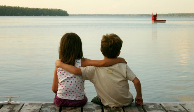 Boy and Girl Sitting by Lake