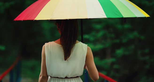 Girl standing alone holding a colorful umbrella in the rain