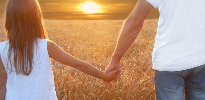 Father holding hands with his daughter at sunset in barley field