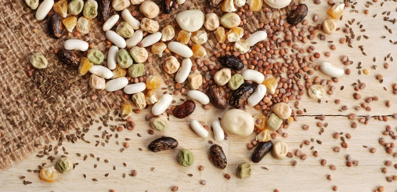 Assorted garden seeds scattered over burlap on rustic wood background.  Seeds include various beans,